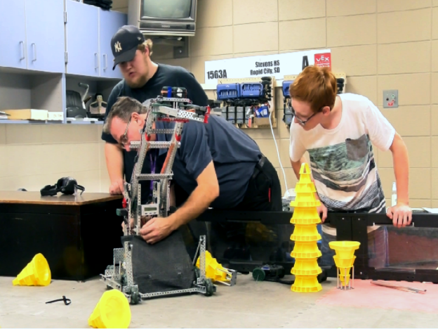 Stevens High School teacher Jason Reub helps students build a robot on Sept. 12, 2017