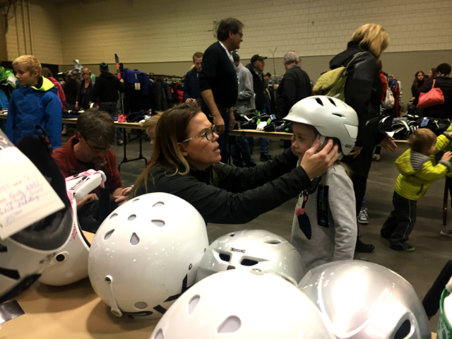 © A women fits a helment to a young boy at the annual Ski Swap benefiting Ski for Light, Nov. 4, 2017.
