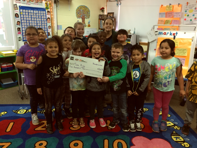 Tara King and her first grade class at Horace Mann Elementary display King's 1+1 Giveaway check on Nov. 6, 2017